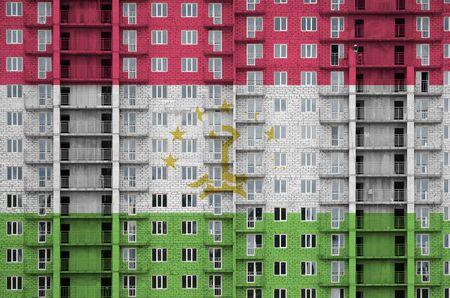 Tajikistan flag depicted in paint colors on multi-storey residental building under construction. Textured banner on big brick wall background