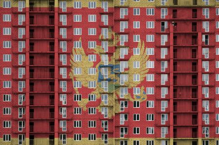 Montenegro flag depicted in paint colors on multi-storey residental building under construction. Textured banner on big brick wall background Archivio Fotografico