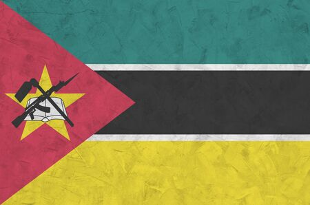 Mozambique flag depicted in bright paint colors on old relief plastering wall close up. Textured banner on rough background Stock fotó