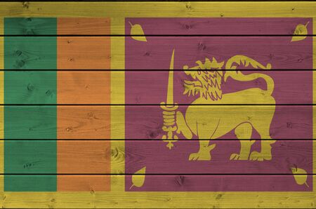 Sri Lanka flag depicted in bright paint colors on old wooden wall close up. Textured banner on rough background
