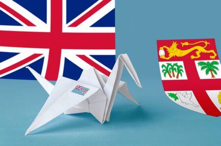 Fiji flag depicted on paper origami crane wing. Oriental handmade arts concept