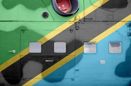 Tanzania flag depicted on side part of military armored helicopter close up. Army forces aircraft conceptual background