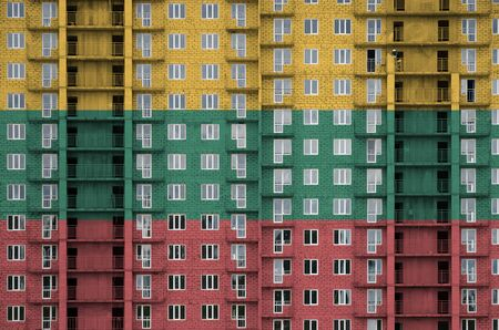 Lithuania flag depicted in paint colors on multi-storey residental building under construction. Textured banner on big brick wall background