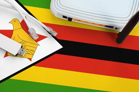 Zimbabwe flag depicted on table with internet rj45 cable, wireless usb wifi adapter and router. Internet connection concept