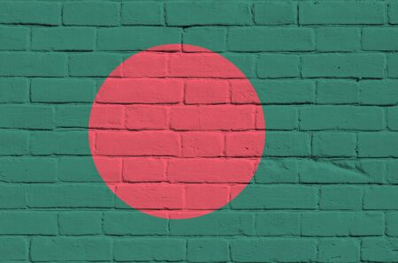Bangladesh flag depicted in paint colors on old brick wall close up. Textured banner on big brick wall masonry background