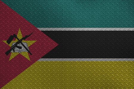 Mozambique flag depicted in paint colors on old brushed metal plate or wall close up. Textured banner on rough background Stock fotó