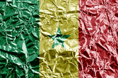 Senegal flag depicted in paint colors on shiny crumpled aluminium foil close up. Textured banner on rough background