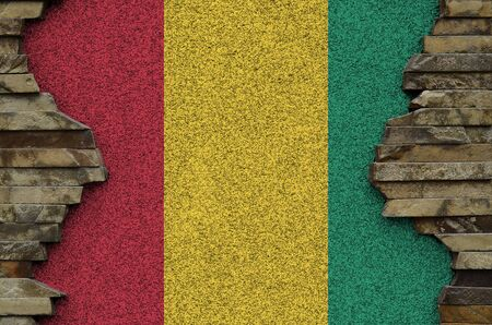 Guinea flag depicted in paint colors on old stone wall close up. Textured banner on rock wall background Stock fotó