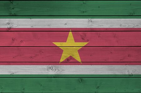 Suriname flag depicted in bright paint colors on old wooden wall close up. Textured banner on rough background