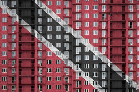 Trinidad and Tobago flag depicted in paint colors on multi-storey residental building under construction. Textured banner on big brick wall background