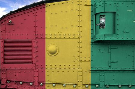 Guinea flag depicted on side part of military armored tank close up. Army forces conceptual background