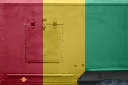Guinea flag depicted on side part of military armored truck close up. Army forces vehicle conceptual background