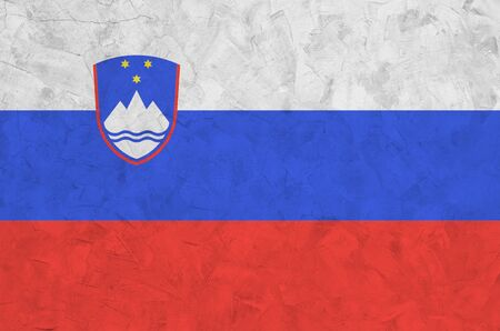 Slovenia flag depicted in bright paint colors on old relief plastering wall close up. Textured banner on rough background
