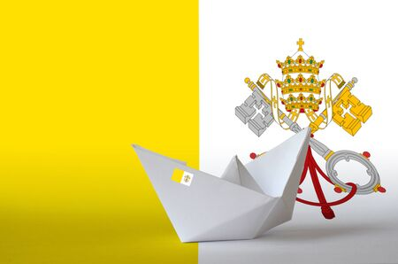 Vatican City State flag depicted on paper origami ship closeup. Oriental handmade arts concept