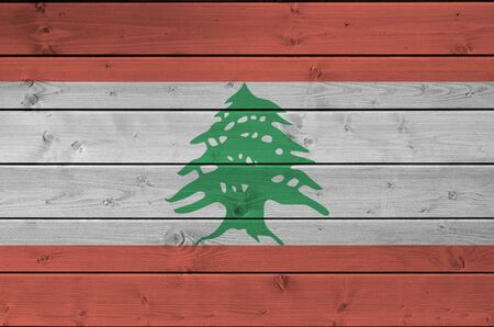 Lebanon flag depicted in bright paint colors on old wooden wall close up. Textured banner on rough background Imagens