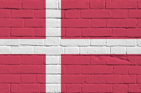 Denmark flag depicted in paint colors on old brick wall close up. Textured banner on big brick wall masonry background