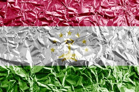 Tajikistan flag depicted in paint colors on shiny crumpled aluminium foil close up. Textured banner on rough background
