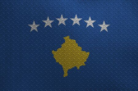 Kosovo flag depicted in paint colors on old brushed metal plate or wall close up. Textured banner on rough background