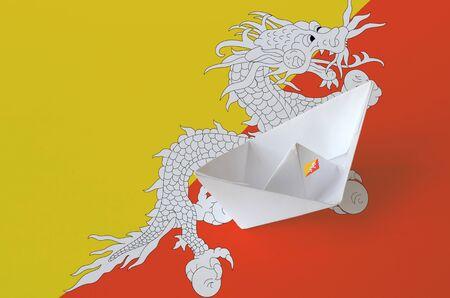 Bhutan flag depicted on paper origami ship closeup. Oriental handmade arts concept Stock Photo