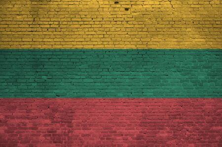Lithuania flag depicted in paint colors on old brick wall close up. Textured banner on big brick wall masonry background