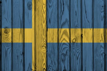 Sweden flag depicted in bright paint colors on old wooden wall close up. Textured banner on rough background