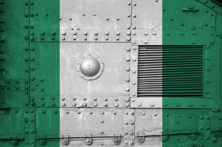 Nigeria flag depicted on side part of military armored tank close up. Army forces conceptual background