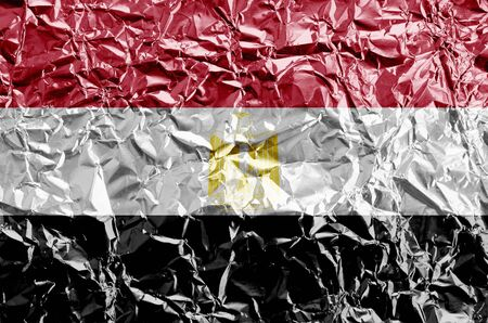 Egypt flag depicted in paint colors on shiny crumpled aluminium foil close up. Textured banner on rough background Banco de Imagens