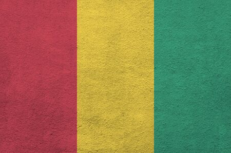 Guinea flag depicted in bright paint colors on old relief plastering wall close up. Textured banner on rough background