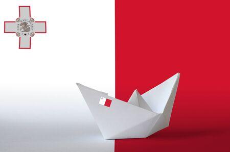 Malta flag depicted on paper origami ship closeup. Oriental handmade arts concept Stock Photo