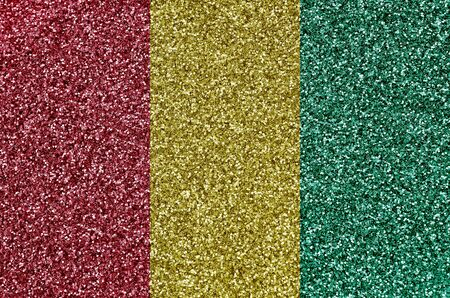 Guinea flag depicted on many small shiny sequins. Colorful festival background for disco party