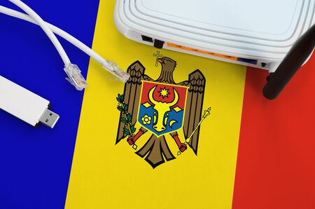 Moldova flag depicted on table with internet rj45 cable, wireless usb wifi adapter and router. Internet connection concept