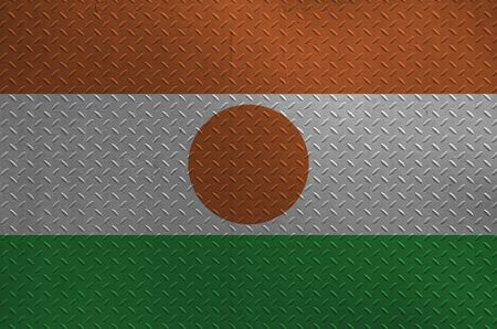 Niger flag depicted in paint colors on old brushed metal plate or wall close up. Textured banner on rough background Stock Photo