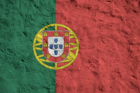 Portugal flag depicted in bright paint colors on old relief plastering wall close up. Textured banner on rough background