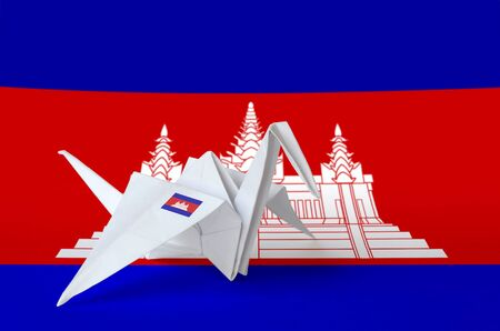 Cambodia flag depicted on paper origami crane wing. Oriental handmade arts concept Stock Photo