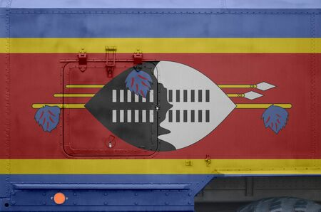 Swaziland flag depicted on side part of military armored truck close up. Army forces vehicle conceptual background