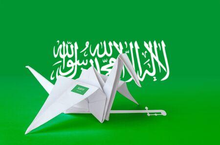 Saudi Arabia flag depicted on paper origami crane wing. Oriental handmade arts concept