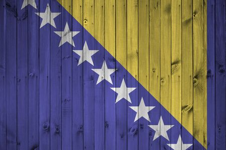 Bosnia and Herzegovina flag depicted in bright paint colors on old wooden wall close up. Textured banner on rough background