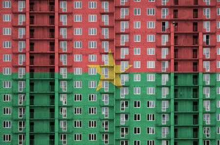 Burkina Faso flag depicted in paint colors on multi-storey residental building under construction. Textured banner on big brick wall background Zdjęcie Seryjne - 135359432