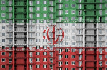 Iran flag depicted in paint colors on multi-storey residental building under construction. Textured banner on big brick wall background Archivio Fotografico