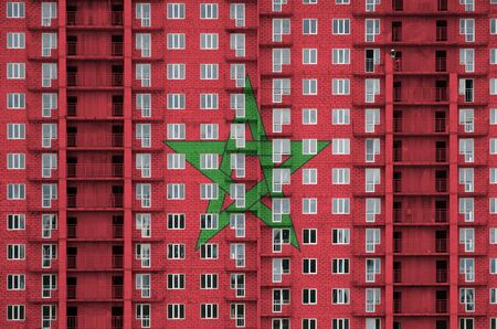 Morocco flag depicted in paint colors on multi-storey residental building under construction. Textured banner on big brick wall background