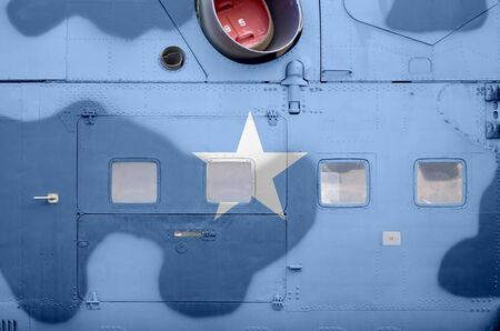 Somalia flag depicted on side part of military armored helicopter close up. Army forces aircraft conceptual background