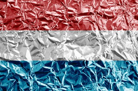 Luxembourg flag depicted in paint colors on shiny crumpled aluminium foil close up. Textured banner on rough background