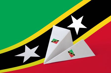 Saint Kitts and Nevis flag depicted on paper origami airplane. Oriental handmade arts concept