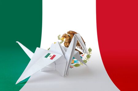 Mexico flag depicted on paper origami crane wing. Oriental handmade arts concept 스톡 콘텐츠