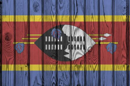 Swaziland flag depicted in bright paint colors on old wooden wall close up. Textured banner on rough background