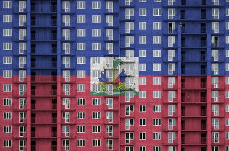 Haiti flag depicted in paint colors on multi-storey residental building under construction. Textured banner on big brick wall background Stock fotó