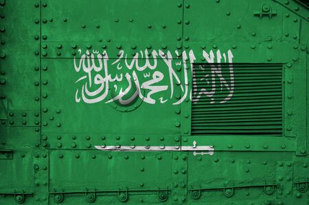 Saudi Arabia flag depicted on side part of military armored tank close up. Army forces conceptual background Stock Photo