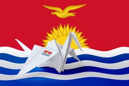 Kiribati flag depicted on paper origami crane wing. Oriental handmade arts concept