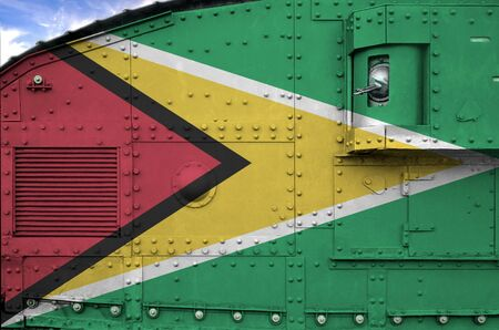 Guyana flag depicted on side part of military armored tank close up. Army forces conceptual background Stock fotó