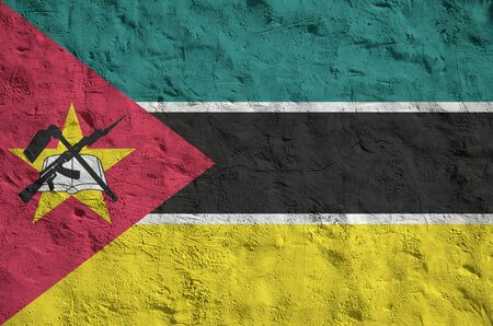 Mozambique flag depicted in bright paint colors on old relief plastering wall close up. Textured banner on rough background